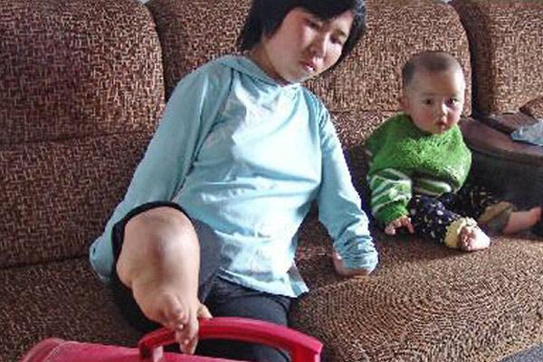 Bà mẹ không tay dùng đôi chân tật nguyền chăm con