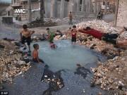 Thế giới - Trẻ em Syria biến hố bom thành hồ bơi giữa phố