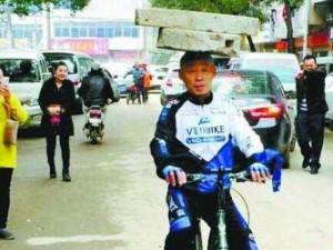 Thế giới - TQ: 13 năm đội cối xay 34kg trên đầu đạp xe trên phố