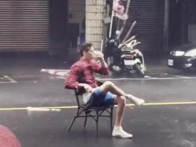 Thản nhiên đọc báo, uống trà trong siêu bão giữa đường phố