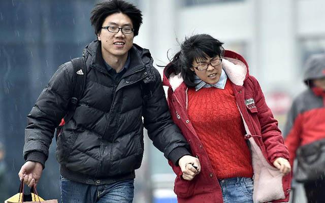 """Một cặp đôi nắm tay nhau chạy trong cơn mưa tới nhà ga Thiên Tân, phía bắc Trung Quốc ngày 15.2.  Người ngoại tỉnh làm ăn xa nhà ở Trung Quốc bắt đầu """"mùa về quê"""" thường niên, thường từ tháng 2 và kết thúc vào tháng 3."""