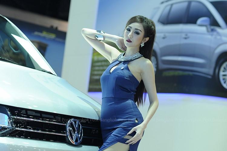 Người đẹp mặc váy xẻ để lộ những điểm sexy khó cưỡng bên cạnh lưới tản nhiệt chiếc ô tô bóng loáng.