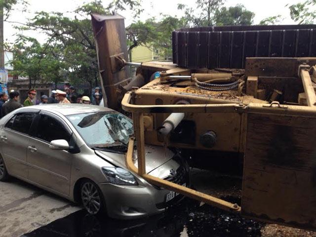Máy ủi rơi từ xe đầu kéo đè bẹp ô tô, tài xế thoát chết - 1