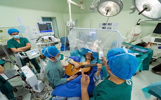 Trung Quốc: Người đàn ông gảy đàn guitar trên bàn mổ - 1