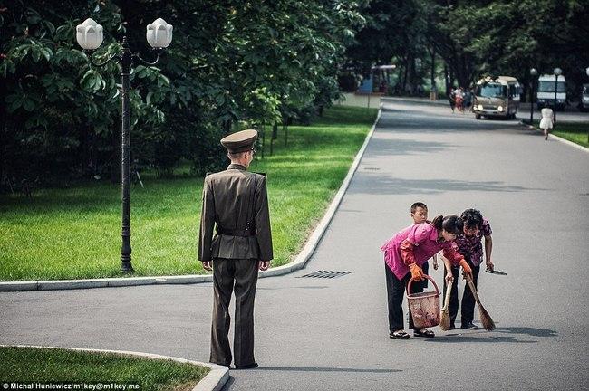Một sĩ quan giám sát việc quét dọn vỉa hè tại một công viên ở thủ đô Bình Nhưỡng.