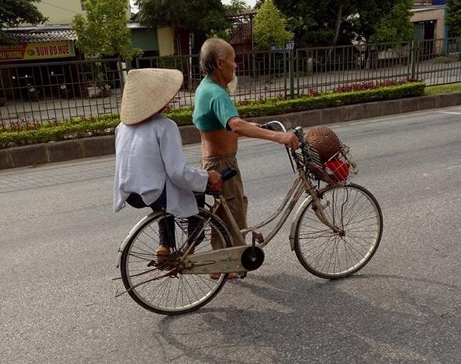 """Tác giả Minh Hiếu đã  """" chộp """"  được khoảnh khắc hạnh phúc rất đỗi giản đơn khi một cụ ông dắt xe đạp chở cụ bà đi bán mít trên phố."""