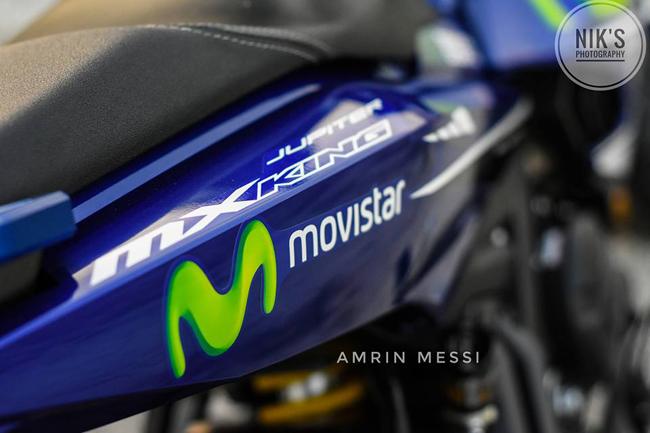 Tem xe màu xanh da trời đặc trưng, kết hợp logo Movistar kèm chữ M nổi bật.