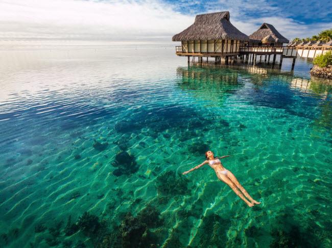 Nữ du khách nằm thư giãn trên mặt nước ngoài khơi đảo Moorea, Tahiti.