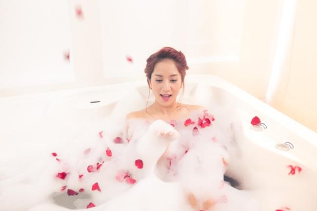 """Khánh Thi từng gây xôn xao khi tự tin khoe hình thể gợi cảm trong MV  """" Ngày anh đến bên em """" . Trong MV, ca sĩ 34 tuổi có nhiều cảnh quay đẹp diện nội y trên giường và dưới bồn tắm rải đầy cánh hoa hồng."""