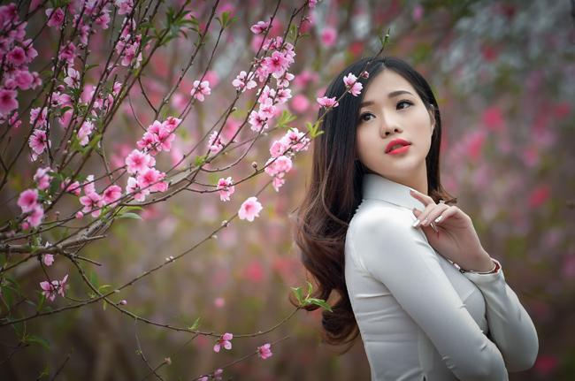 Lưu giữ vẻ đẹp thanh xuân mơn mởn bên nhành đào Tết đã trở thành sở thích của nhiều cô gái.