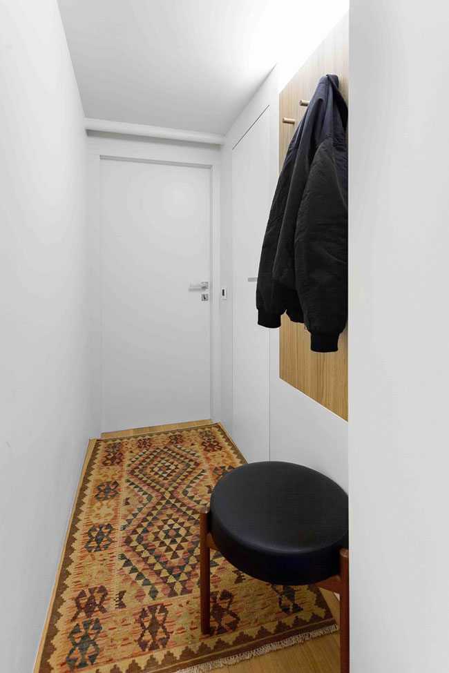 Ngay cửa ra vào của căn hộ được bài trí một tấm thảm màu sắc sặc sỡ nhằm mang lại không khí vui vẻ và cảm giác ấm áp cho căn hộ. Bức tường dọc hành lang vào căn hộ được biến tấu thành nơi treo áo khoác.
