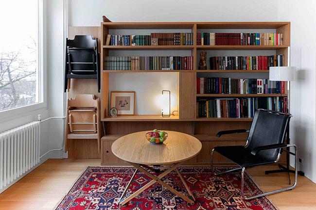 Giá sách được thiết kế dọc theo toàn bộ bức tường trong không gian giữa khối bếp và cửa sổ, đây sẽ được coi là phòng khách nên cửa sổ được để thoáng rộng nhằm lấy ánh sáng tự nhiên. Cấu trúc của giá sách được bài trí sáng tạo và hiện đại ngoài việc để sách, báo còn là nơi để trang trí cho căn phòng và có chỗ treo ghế ngồi cho khách một cách rất thông minh.