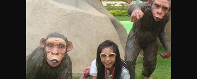 Ảnh quá khứ Thủy Tiên chụp tại một khu công viên giải trí. Cô bắt chước tạo dáng giống như tượng của một chú khỉ trên bãi cỏ.