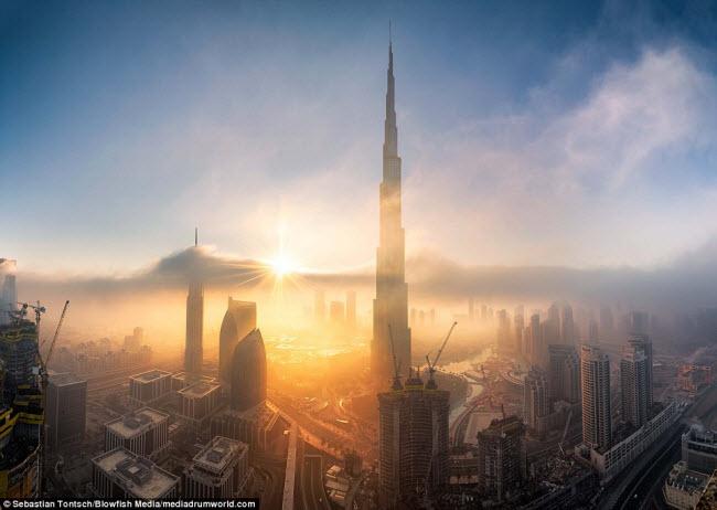 Những tia nắng đầu tiên trong ngày xuất hiện phía chân trời giúp xua tan màn sương sớm bao phủ những toà nhà chọc trời, bao gồm tòa nhà cao nhất thế giới Burj Khalifa.