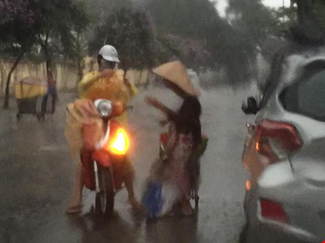 Cô gái dừng xe giữa trời mưa lớn mặc áo mưa cho cụ già - 1