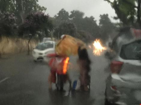 Cô gái dừng xe giữa trời mưa lớn mặc áo mưa cho cụ già - 2
