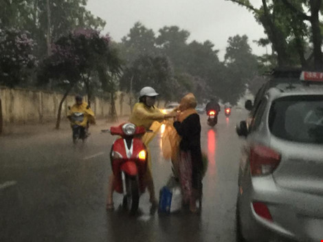 Cô gái dừng xe giữa trời mưa lớn mặc áo mưa cho cụ già - 3