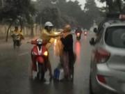 Cô gái dừng xe giữa trời mưa lớn mặc áo mưa cho cụ già