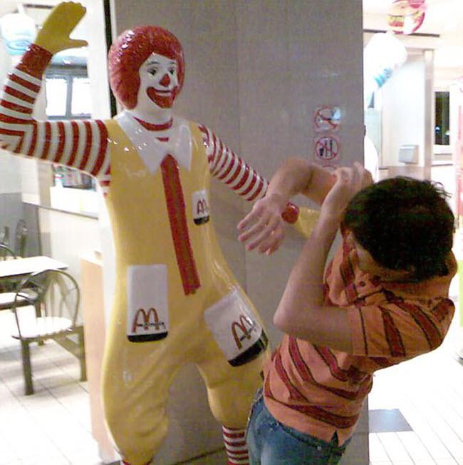 Khách hàng tỏ vẻ sợ hãi khi đứng trước tượng chú hề Ronald McDonald đang giơ tay trong một nhà hàng McDonald.
