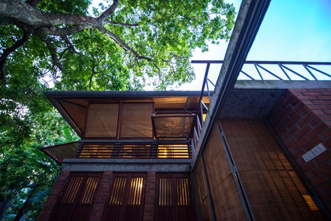 Giữa khu phố thị ồn ào, ngôi nhà như đưa người ta về một vùng quê yên bình, với nhà tranh, sân rộng và khu vườn rợp bóng cây xanh.