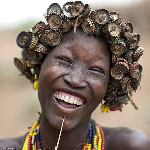 Một cô gái của bộ tộcDaasanachniềm nở khi khoe bộ tóc giả nắp chai của mình.
