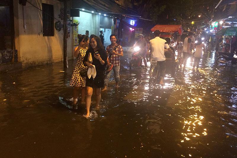 HN: Mưa xối xả, khách nước ngoài thích thú dạo trên... phố ngập - 1
