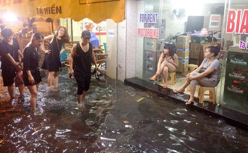 HN: Mưa xối xả, khách nước ngoài thích thú dạo trên... phố ngập - 2