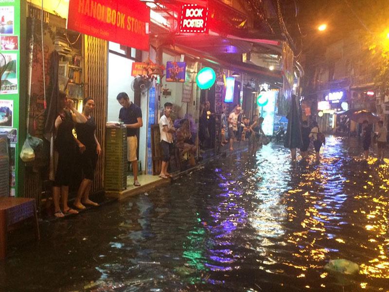 HN: Mưa xối xả, khách nước ngoài thích thú dạo trên... phố ngập - 3