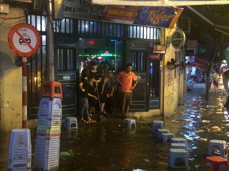 HN: Mưa xối xả, khách nước ngoài thích thú dạo trên... phố ngập - 4