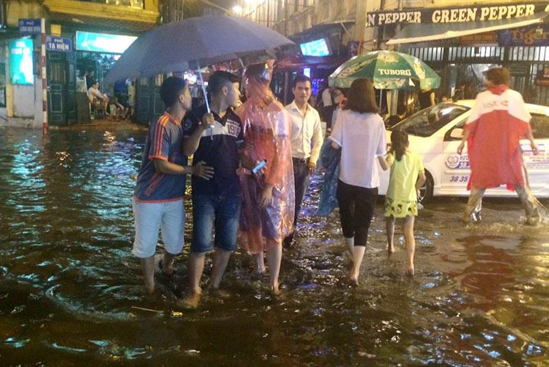 HN: Mưa xối xả, khách nước ngoài thích thú dạo trên... phố ngập - 5
