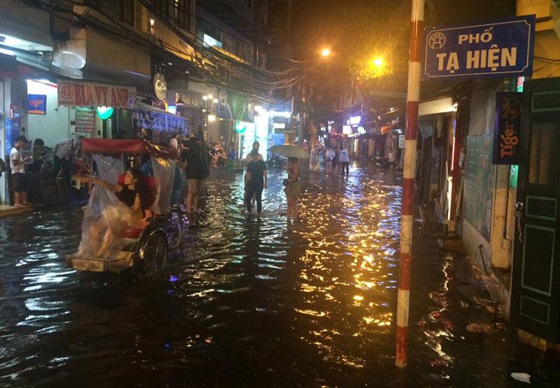 HN: Mưa xối xả, khách nước ngoài thích thú dạo trên... phố ngập - 6