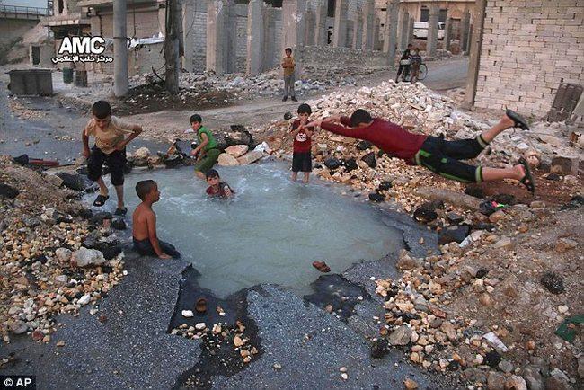 Trẻ em Syria biến hố bom thành hồ bơi giữa phố - 1