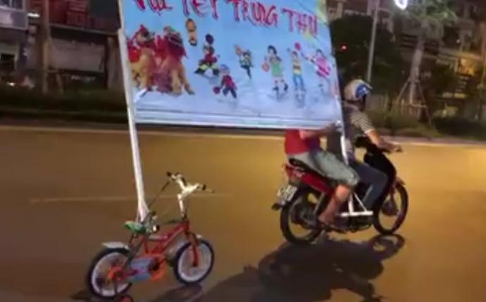 Pha chở biển quảng cáo bằng xe đạp 4 bánh náo loạn Hà Nội - 1