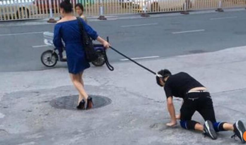 Người phụ nữ dắt người đi dạo trên phố như chó cưng - 1