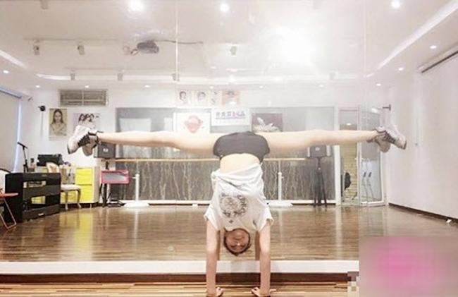 """Nhờ vào việc tập luyện yoga nên Jin có thể dễ dàng xoạc chân 180 độ ngay cả với tư thế  """" trồng cây chuối """" ."""