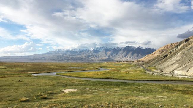 Cánh đồng cỏ xanh mướt xuất hiện dọc tuyến đường Karakoram với dãy núi Thiên Sơn ở phía xa.