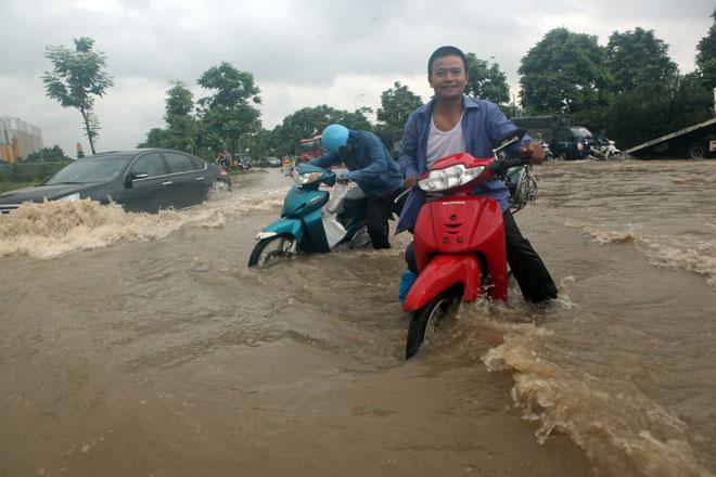 Đại lộ Thăng Long ngập sâu, dân xếp hàng thuê người chở xe - 4