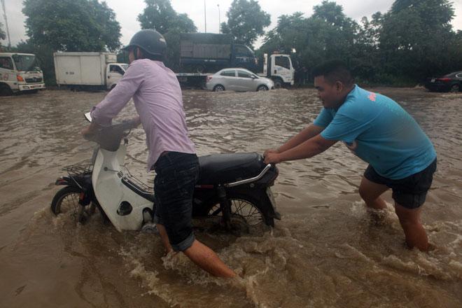 Đại lộ Thăng Long ngập sâu, dân xếp hàng thuê người chở xe - 10