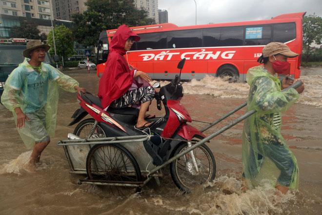 Đại lộ Thăng Long ngập sâu, dân xếp hàng thuê người chở xe - 7