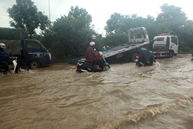Đại lộ Thăng Long ngập sâu, dân xếp hàng thuê người chở xe - 9