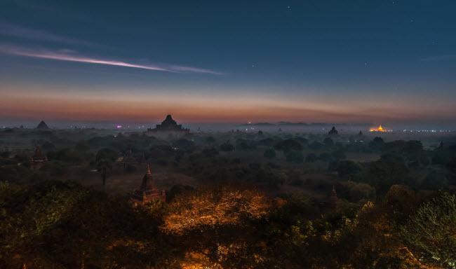 Khung cảnh lúc sáng tinh mơ trên những ngôi đền cổ nằm giữa rừng cây rộng lớn.