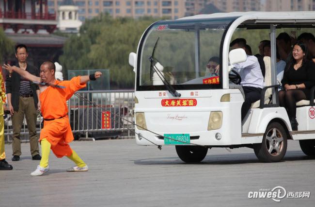 Hu Qiong, được mệnh danh là  La Hán sắt , kéo một chiếc xe điện chở 12 người với chiếc dao sắc ở cổ.