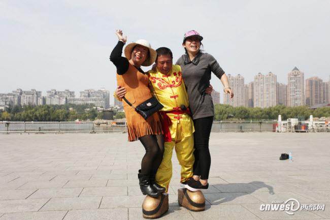 Zhang Zhenghui, có biệt danh là  Vua giày sắt , đi đôi giày bằng sắt nặng 123 kg bước đi với hai người nữ đứng trên giày.