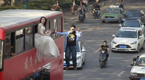 Cô gái mặc váy cưới treo mình lơ lửng trên xe buýt - 1
