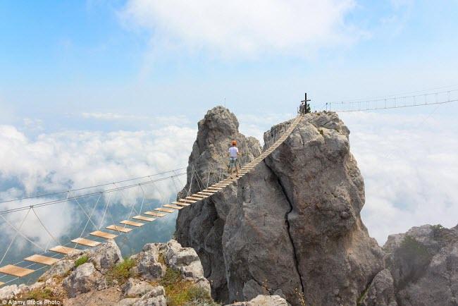 Nếu muốn ngắm toàn cảnh vùng núi Ai-Petri trên bán đảo Crimea, bạn đầu tiên phải có đủ can đảm đi qua cây cầu với sàn bằng gỗ bác qua hẻm núi ở đây.