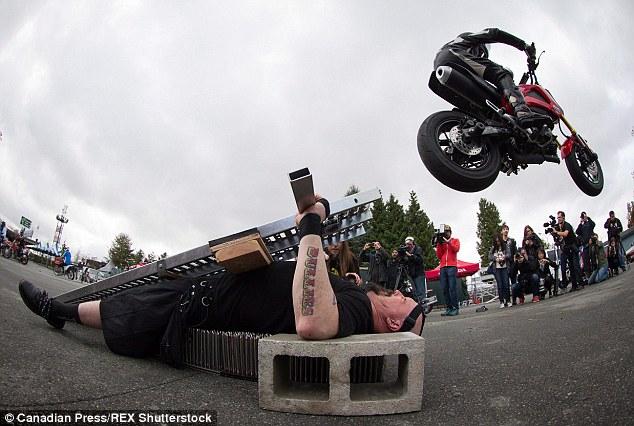 Nằm trên đinh nhọn để 70 xe máy chạy qua người - 1