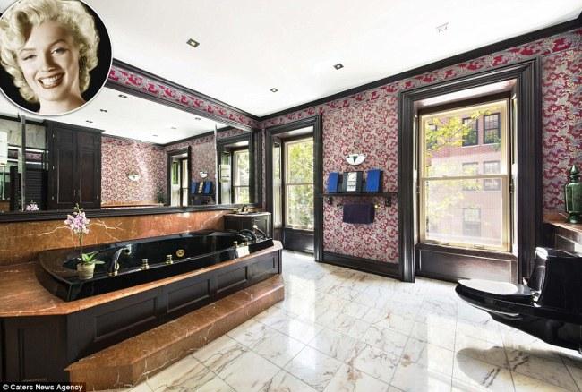 Phòng tắm của Marilyn trong căn hộ nhà vườn ở & nbsp;New York & nbsp;ấn tượng với & nbsp;bồn & nbsp;tắm lớn bằng & nbsp;cẩm thạch màu & nbsp;đen. Viền cửa, bồn rửa, sàn nhà, thang vào bồn tắm và & nbsp;các vật dụng khác cũng đều làm từ đá cẩm thạch. Tường phòng tắm được trang trí hoa văn tỉ mỉ, mang phong cách hoàng gia.
