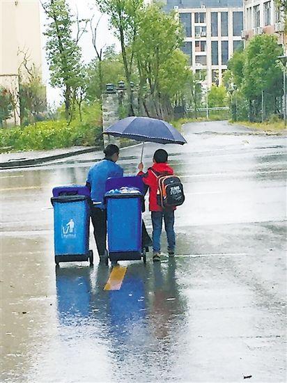 Cảm động bé 7 tuổi che ô, kéo rác cho người lao công - 1