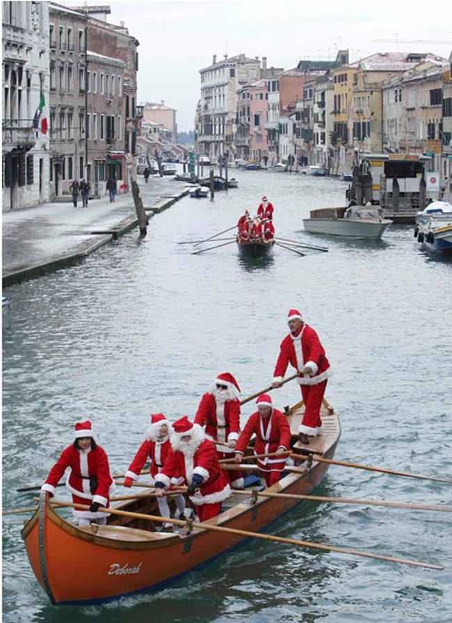 Những ông già Noel chèo thuyền trên một dòng kênh ở thành phố Venice thơ mộng của nước Ý ngày 17.12.
