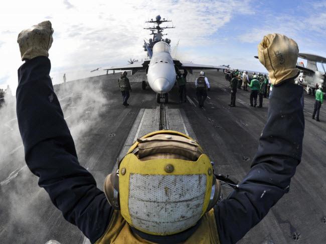 Một binh sĩ chỉ dẫn chiến đấu cơ F/A-18C Hornet vào bệ phóng trên tàu sân bay USS Harry S. Truman.